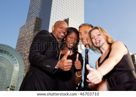 A group of business people giving a thumbs up sign - stock photo