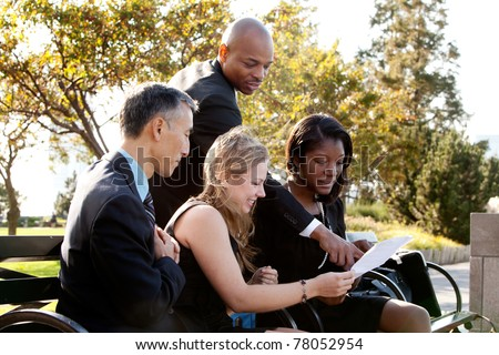 A group of business people in a park setting - stock photo