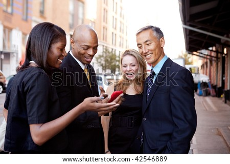 A group of business people looking at a cell phone and laughing