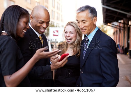 A group of business people looking at a cell phone and laughing - stock photo