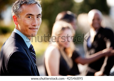 A group of business people outside - sharp focus on Asian man in foreground - stock photo