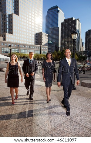 A group of business people walking down town in a large city - stock photo
