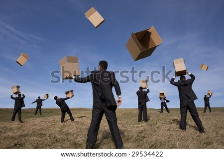 a group of businessman in the field with cardboard boxes (some motion blur on fast movement) - stock photo