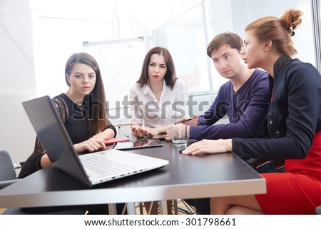 a group of businessmen sitting at the desk in the office, watching something on a laptop