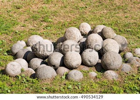 A group of cannonballs in white stone on a green lawn. Milan, Italy