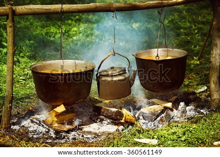 A group of cauldrons and kettle are hanged upon fire at tourist camp at green summer outdoors background. - stock photo