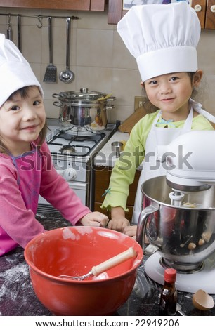 A group of children cooking up something in the kitchen. - stock photo