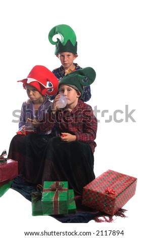 A group of children gathered around some Christmas gifts on the floor enjoying some fresh baked cookies and a glass of milk