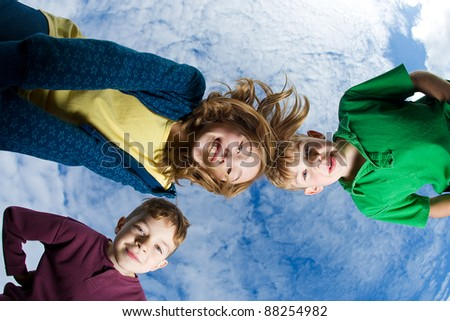 A group of children huddled up and looking down under a blue sky with high clouds. - stock photo