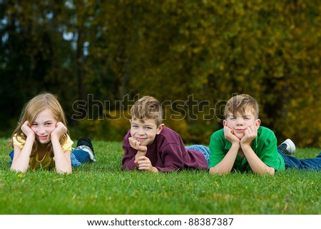 A group of children laying down in the grass. - stock photo