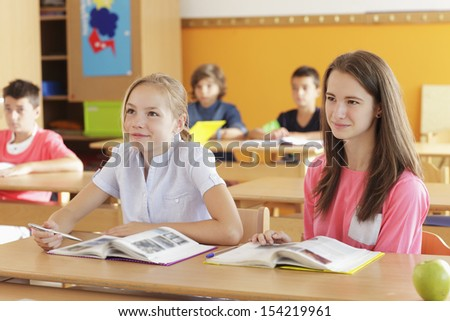 A group of children sitting in the classroom and writing