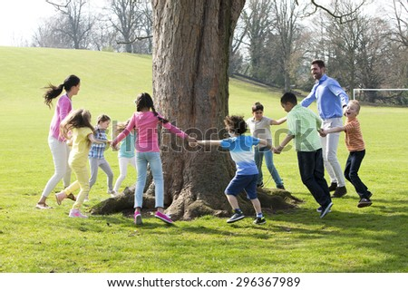 A group of children with two adults holding hands and dance around the trunk of a tree.  - stock photo