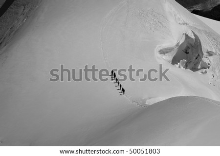 A group of climbers en route in an alpine world. Black & white photo - stock photo