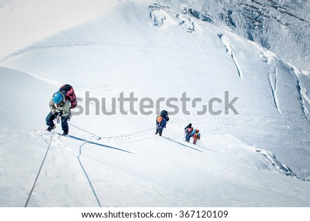 A group of climbers reaching the summit - stock photo