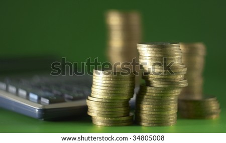 A group of coins and calculator on the green background