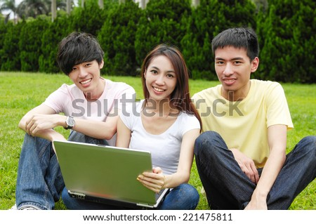 A group of college friends sitting holding laptop with books on campus - stock photo