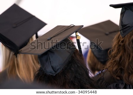 A group of college or high school graduates wearing the traditional cap and gown.  Shallow depth of field. - stock photo