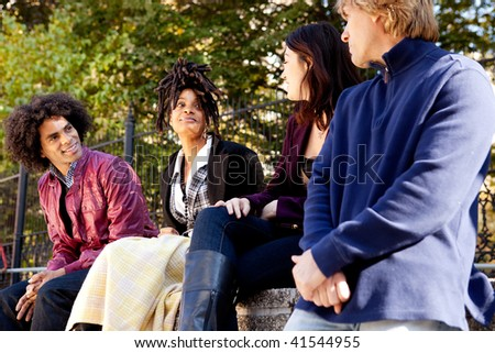 A group of college or university students visiting and having fun - stock photo