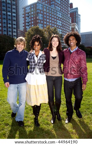A group of college students in a park - shot against the sun with solar flare - stock photo