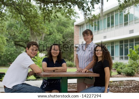 a group of college students relax outside a classroom building - stock photo