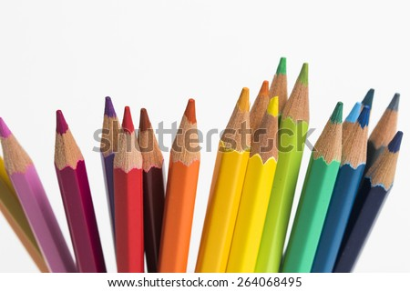 A group of color pencils in a rainbow arrangement on a white isolated background