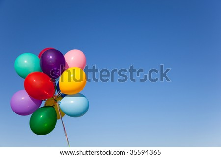 A group of colorful balloons with blue sky background - stock photo