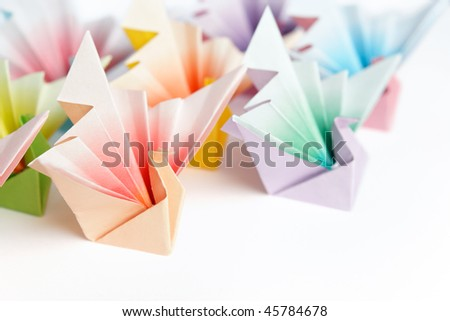 A group of colorful origami birds facing the same direction, on a white background. High key and shallow depth of field. - stock photo