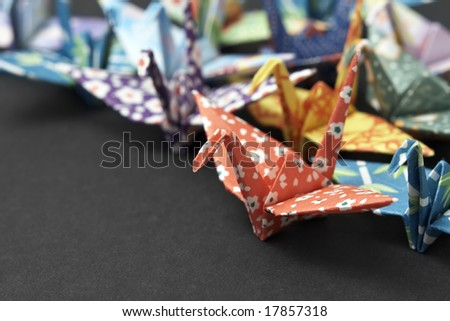 A group of colorful origami cranes on a black background - stock photo