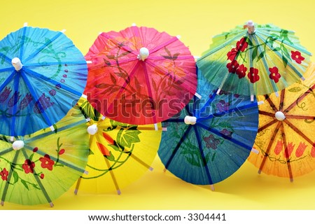 A group of colorful paper drink umbrellas against a yellow background. - stock photo
