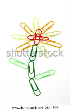 A group of coloured paperclips organized in the form of a yellow flower - stock photo