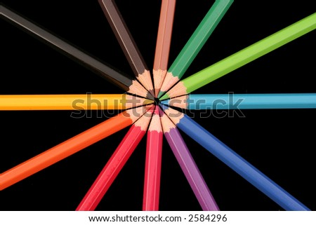 A group of coloured pencils arranged in a star pattern on a back background. - stock photo