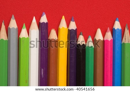 A group of colours pencils on red backgrounds - stock photo