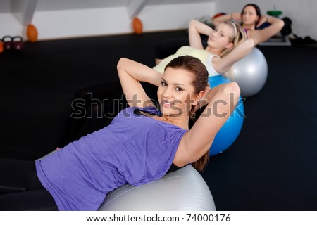 A group of cute girls doing sit ups at a fitness club - stock photo