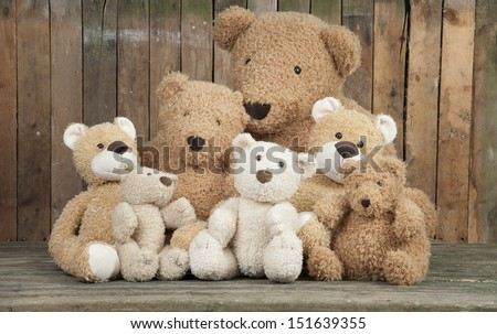 a group of cute teddy bears sitting together against an old wooden wall - stock photo