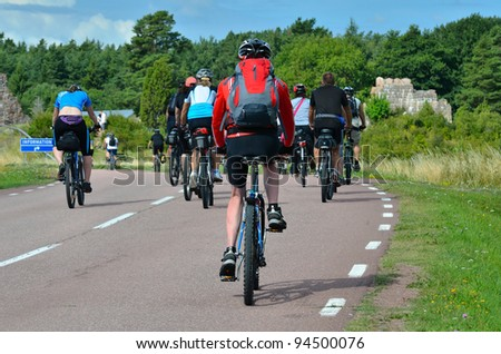 A group of cyclists going on the road in the countryside - stock photo