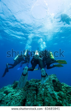A group of diver doing safety stop near sea surface - stock photo