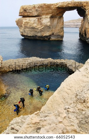 A group of divers comes out from Mediterranean sea near cliffs in Gozo in Malta - stock photo