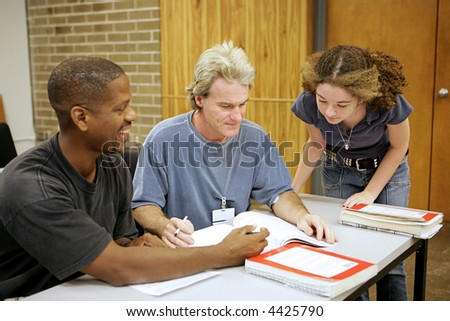 A group of diverse adult education students going over an assignment. - stock photo