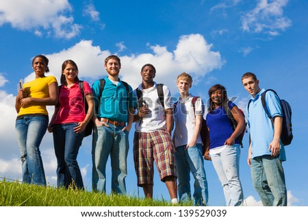 A group of diverse college students/friends outside on a hill with a sky background - stock photo