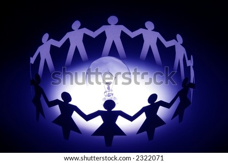 A group of diversify paper chain people surrounding a light bulb. - stock photo