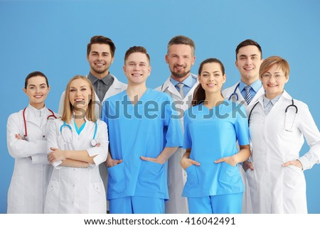 A group of doctors and nurses standing in the hospital, indoors - stock photo