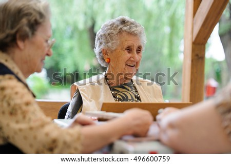 A group of eldelry woman playing rummy