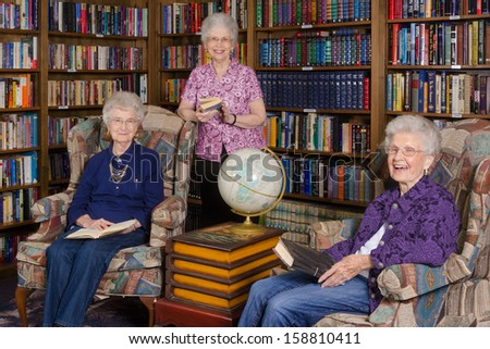 A group of elderly women in an assisted living's residence library - stock photo