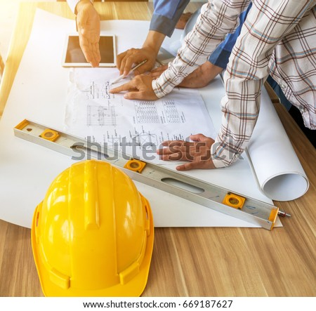 Group engineers looking blueprint construction on stock photo a group of engineers are looking at a blueprint for construction on the table engineering malvernweather Gallery
