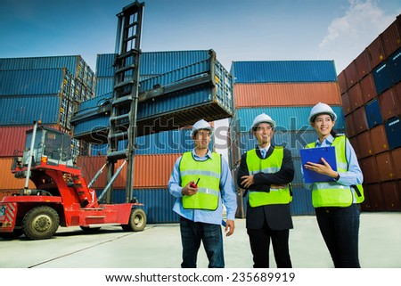 A group of engineers working happily. The cargo container - stock photo