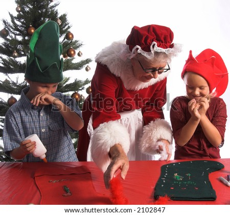 A group of excited young children aged 6 - 12 wearing elf hats and working with Mrs. Santa Claus on a Christmas craft project of decorating a stocking