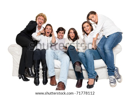 A group of family members sitting at home watching nervously TV - stock photo