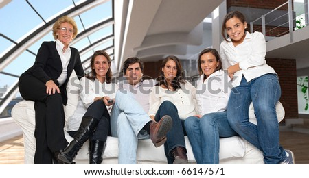 A group of family members sitting on a sofa in a luxurious loft, looking attentively at the camera with a remote control - stock photo