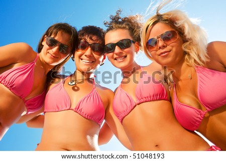 a group of females in bikinis together on the beach with sunglasses