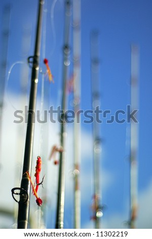 A group of fishing poles ready for use, against blue cloudy sky